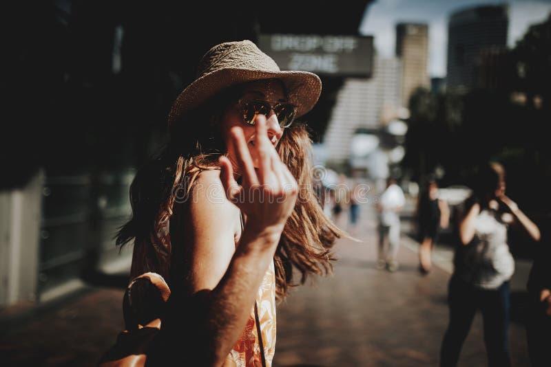 Glückliche Frau, die in Sydney City geht, sich herum dreht und ein Folgungszeichen zur Kamera macht stockbilder
