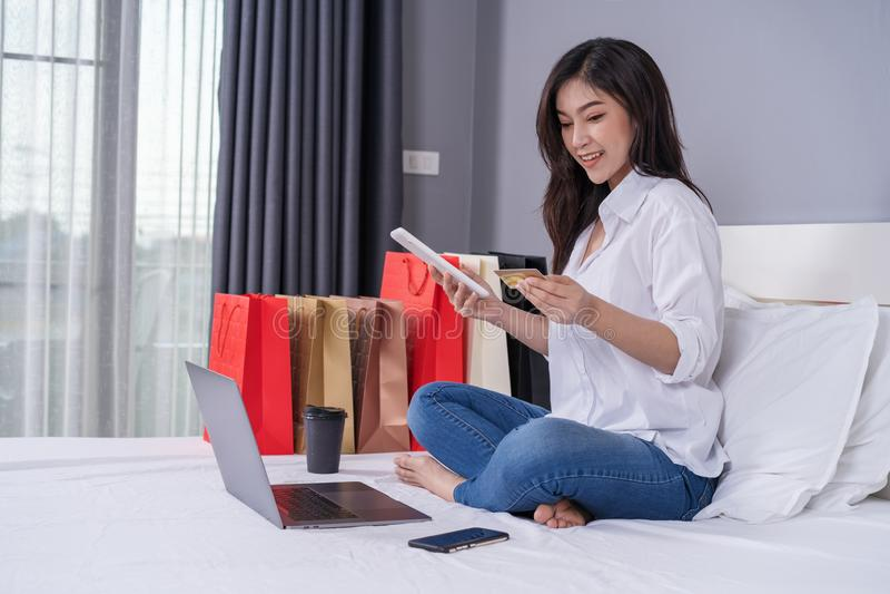 Glückliche Frau, die an Tablette für das on-line-Einkaufen mit Kreditkarte verwendet lizenzfreie stockfotografie