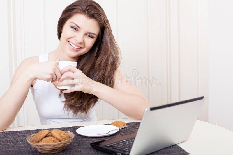 Glückliche Frau, die Tee und Plätzchen genießt stockfotos