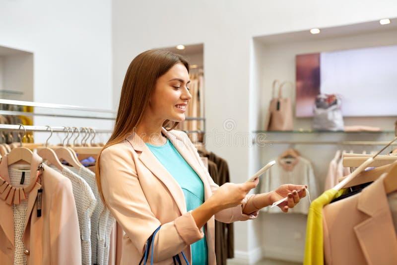 Glückliche Frau, die Telefon-APP am Bekleidungsgeschäft verwendet stockfotografie