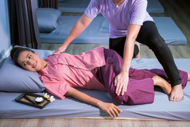 Glückliche Frau, die thailändische Massage im Badekurort hat stockfoto