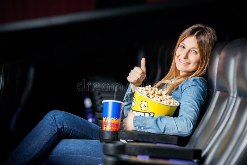 Glückliche Frau, die Thumbsup am Kino-Theater zeigt stockbild