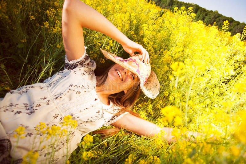 Glückliche Frau, die unter gelben Wildflowers liegt lizenzfreies stockbild