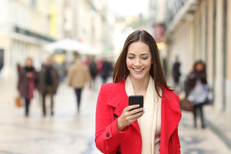 Glückliche Frau, die unter Verwendung eines Mobiltelefons in der Straße geht stockfotografie