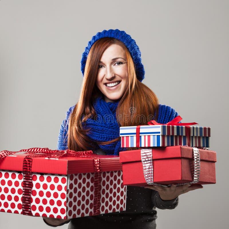 Glückliche Frau, die viele Weihnachtsgeschenke hält lizenzfreie stockfotos