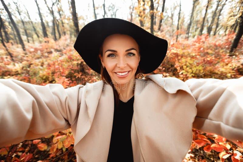Glückliche Frau, die voll selfie im Herbstpark von gelben Blättern macht stockfotos