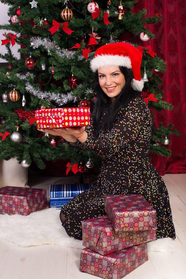 Glückliche Frau, die Weihnachtsgeschenke zeigt lizenzfreie stockfotografie