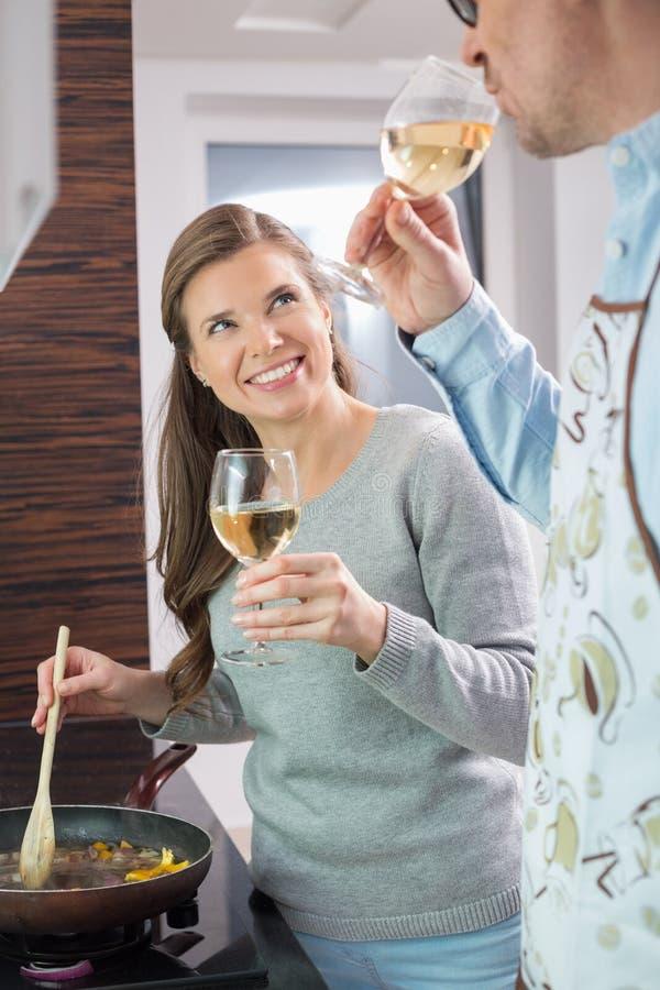 Glückliche Frau, Die Wein Mit Mann Beim Kochen In Der Küche Isst ...
