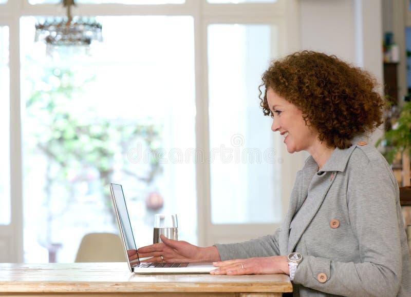 Glückliche Frau, die zu Hause am Schreibtisch unter Verwendung des Laptops sitzt stockfotos