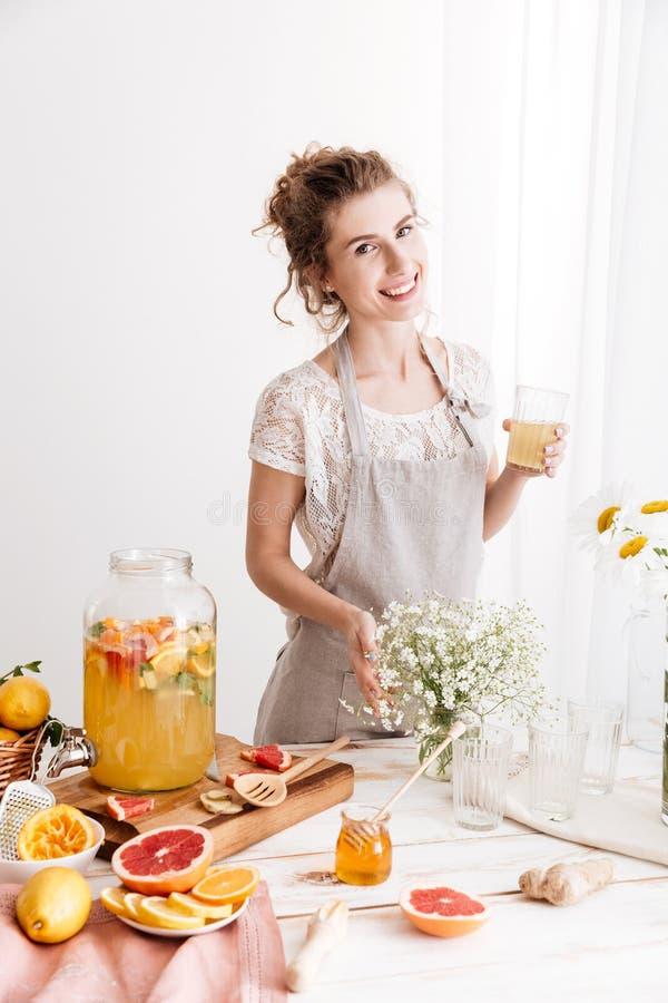Glückliche Frau, die zuhause trinkendes Zitrusfruchtgetränk steht lizenzfreie stockfotografie