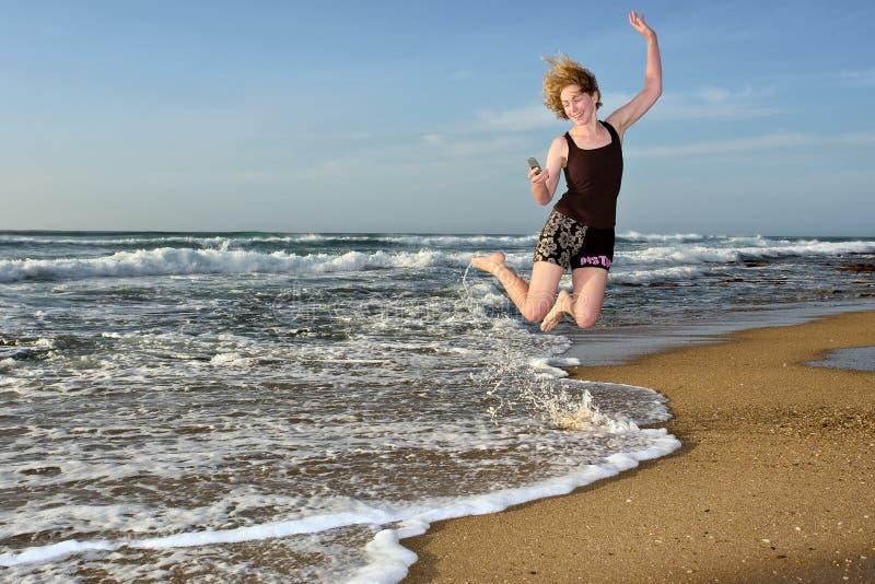 Glückliche Frau fliegt mit mit Handy auf Strand lizenzfreies stockbild