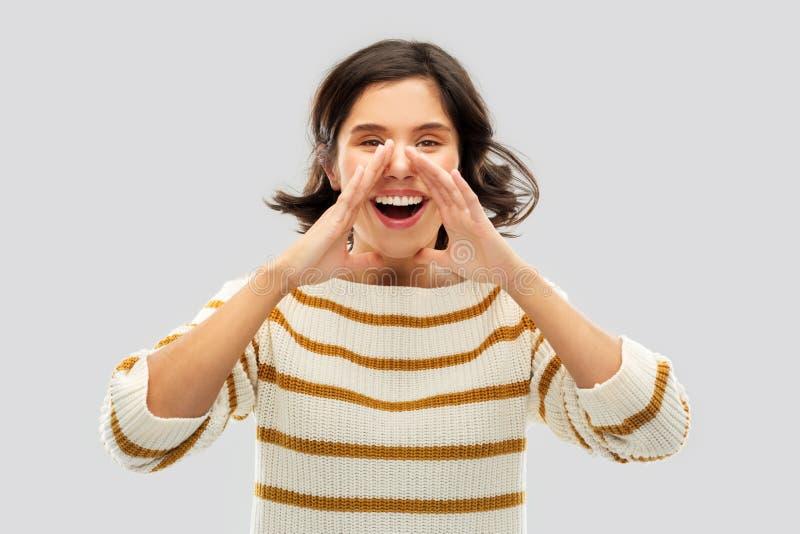 Glückliche Frau in gestreiftem Pullover jemand anrufend lizenzfreies stockfoto