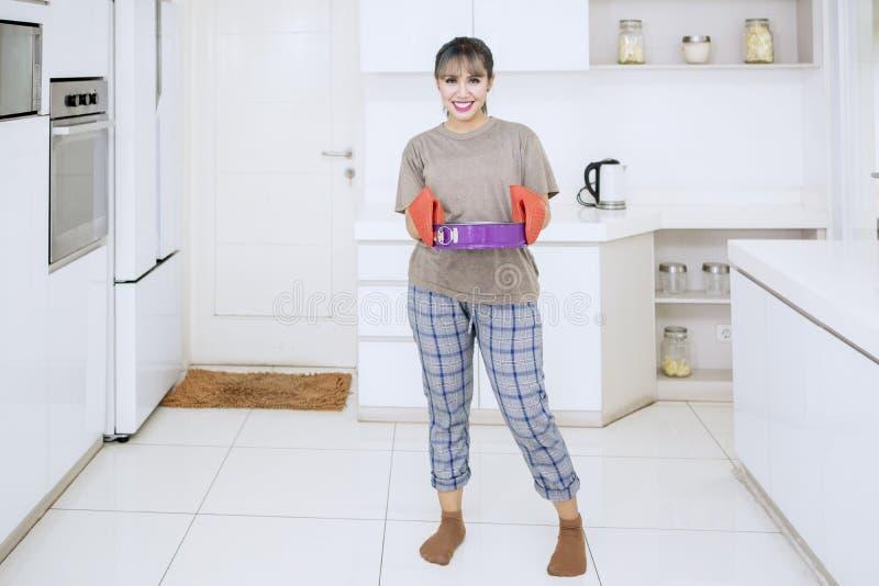 Glückliche Frau hält ein Backblech in der Küche lizenzfreies stockbild