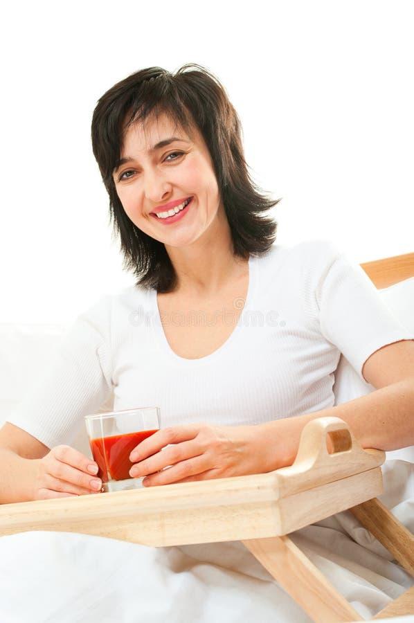 Glückliche Frau im Bett mit Tomate lizenzfreie stockfotografie
