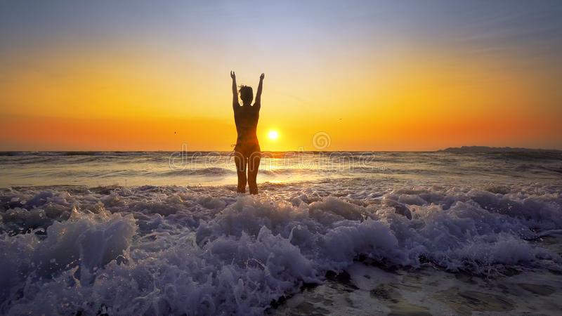 Glückliche Frau im Bikini, der in Seesonnenuntergang springt lizenzfreie stockfotos