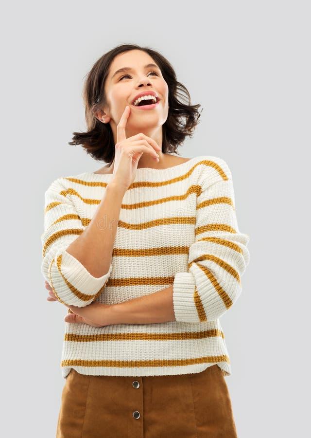 Glückliche Frau im gestreiften Pullover, der oben schaut stockbild