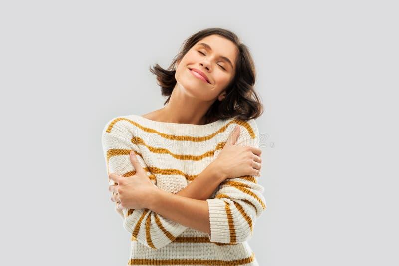 Glückliche Frau im gestreiften Pullover, der sich umarmt stockfotos