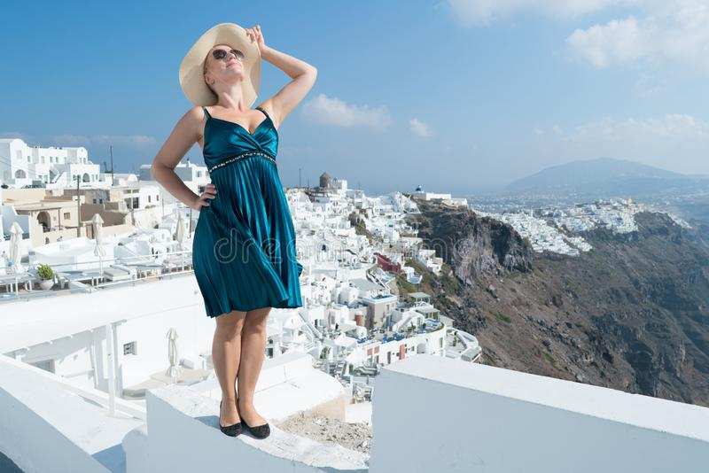 Glückliche Frau im grünen Kleider- und Sonnenhut ihre Feiertage auf Santorini, Griechenland genießend Ansicht über Kessel und Ägä stockbild