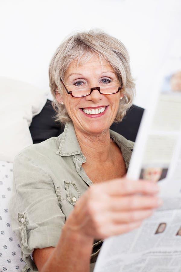Glückliche Frau im Ruhestand, welche die Zeitung liest lizenzfreie stockbilder