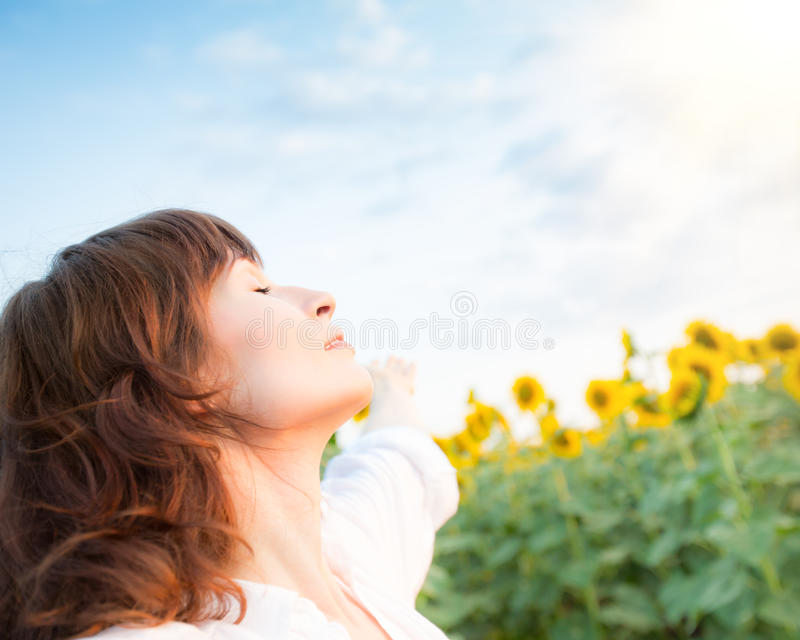 Glückliche Frau im Sonnenblumenfeld lizenzfreies stockbild