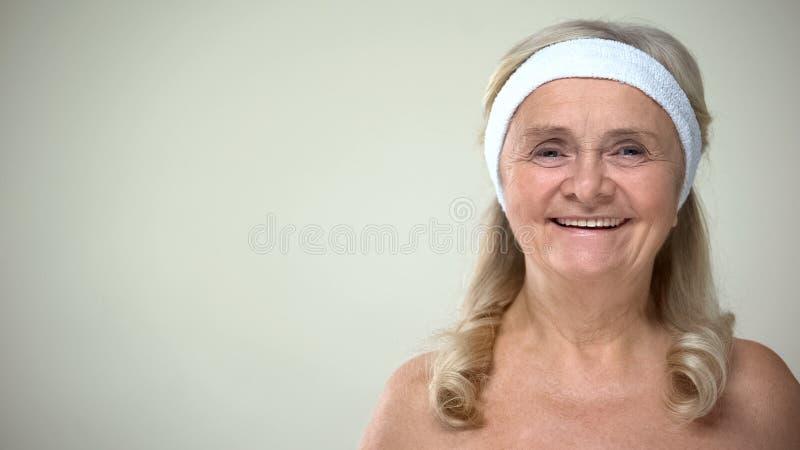 Glückliche Frau im Stirnband lächelnd auf Kamera, Gesichts-skincare Programm, Cosmetology stockfotos