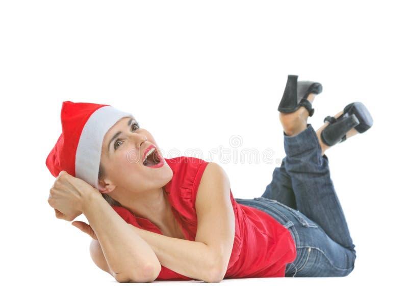 Glückliche Frau im Weihnachtshut, der auf Fußboden legt stockbild