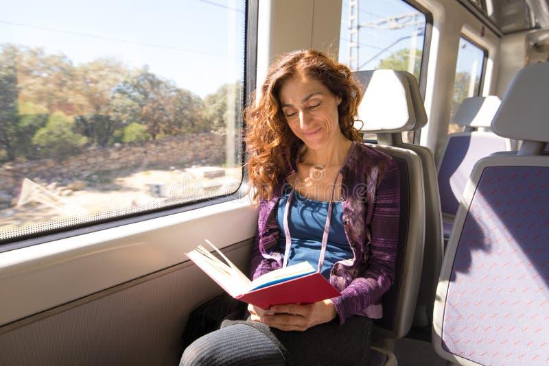 Glückliche Frau im Zuglesebuch lizenzfreies stockfoto