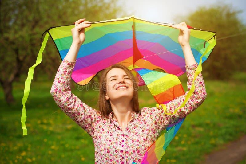 Glückliche Frau ist Fling ein Drachen auf einer Frühlingswiese stockfoto