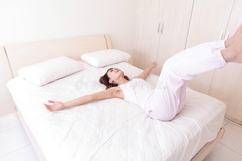 Glückliche Frau legen sich auf ihrem Bett hin lizenzfreies stockfoto