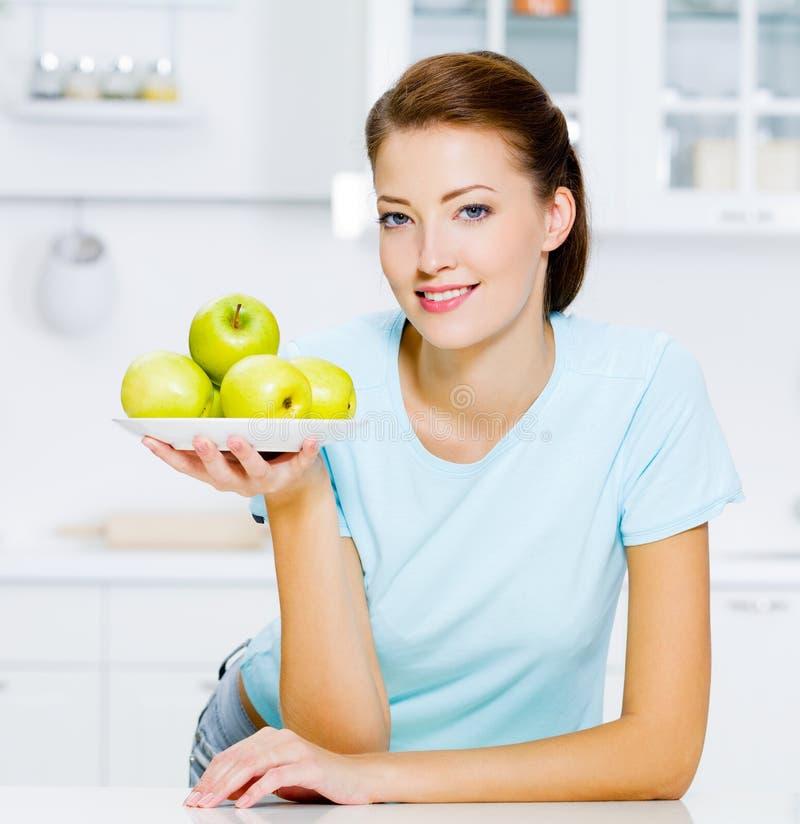Glückliche Frau mit Äpfeln auf einer Platte lizenzfreie stockfotos