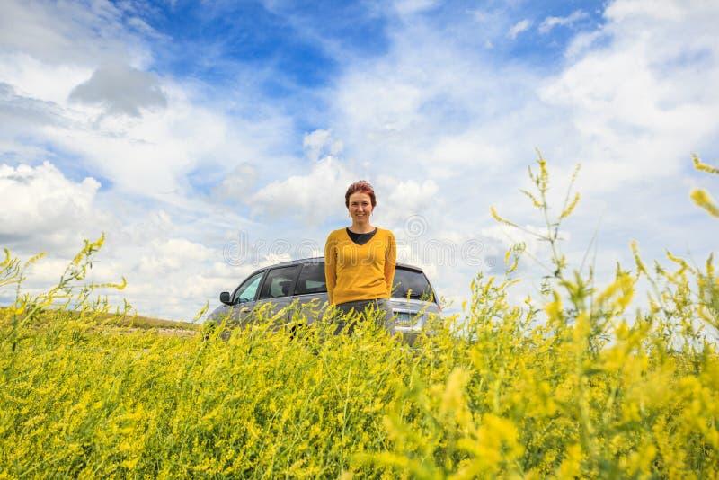 Glückliche Frau mit Auto unter Canolafeld stockbild