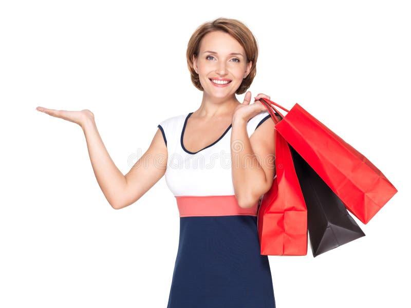 Glückliche Frau mit Darstellungsgeste und -Einkaufstaschen stockbild