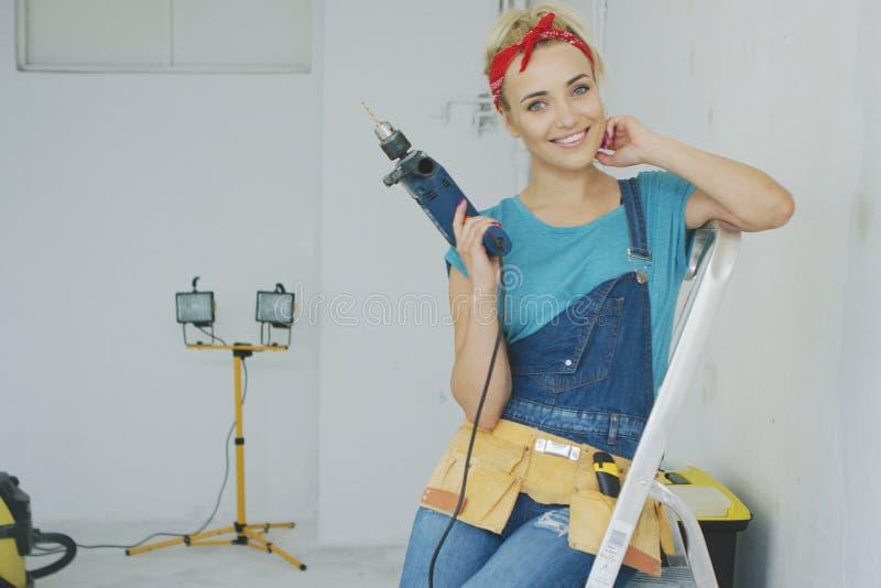 Glückliche Frau mit dem Bohrgerät, das auf Stehleiter sitzt lizenzfreies stockbild