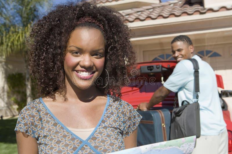 Glückliche Frau mit dem Mann, der Gepäck im Auto hält