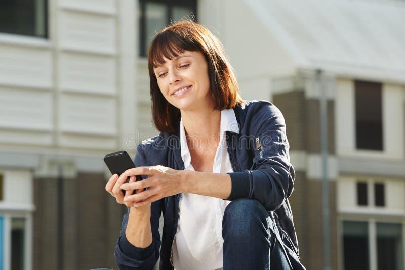 Glückliche Frau mit dem Mobiltelefon, das draußen sitzt stockfoto