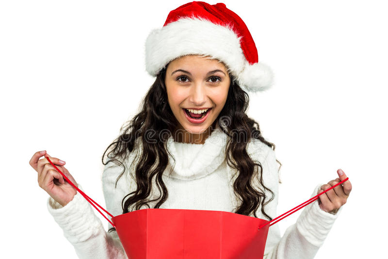 Glückliche Frau mit dem Weihnachtshut, der rote Einkaufstasche öffnet lizenzfreie stockbilder