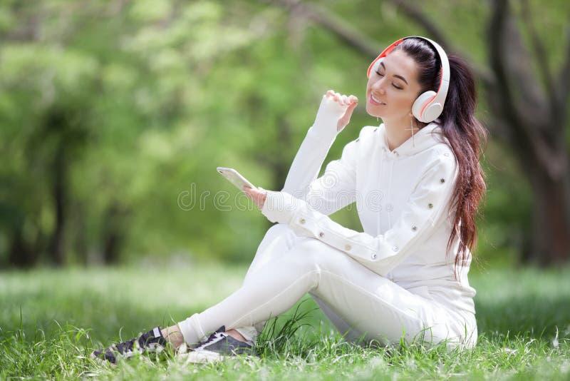 Glückliche Frau mit den Kopfhörern, die im Park sich entspannen Sch?nheitsnaturszene mit buntem Hintergrund Modefrau, welche die  stockfotos