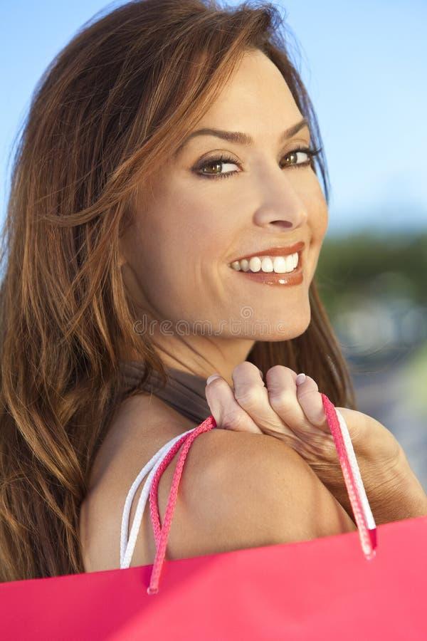 Glückliche Frau mit den rosafarbenen und weißen Einkaufen-Beuteln stockfotos
