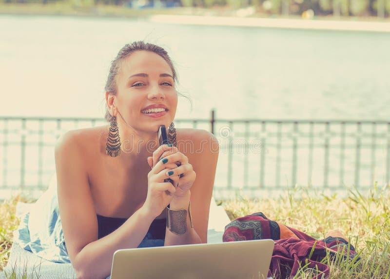 Glückliche Frau mit der Laptop-Computer und Handy, die in einem Park sich entspannen stockbild