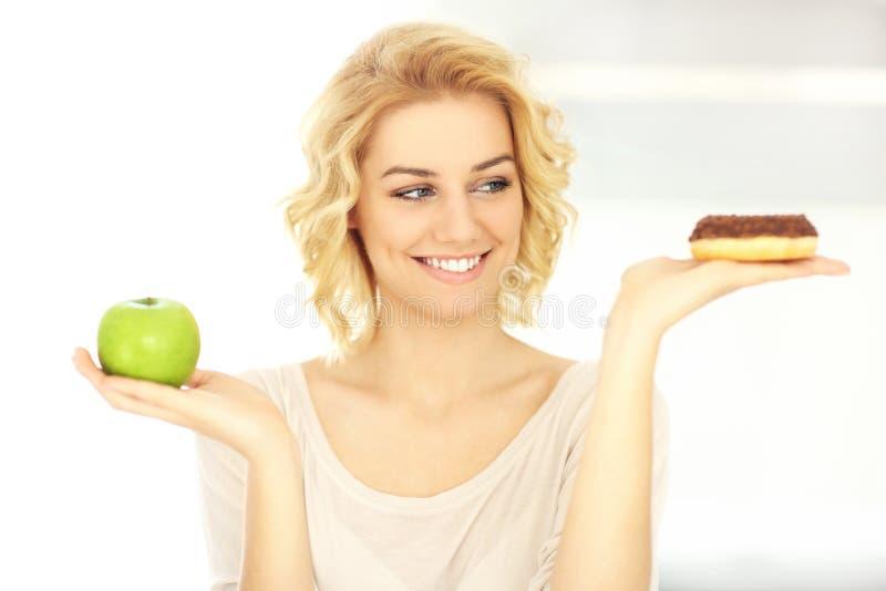 Glückliche Frau mit Donut und Apfel stockfotografie