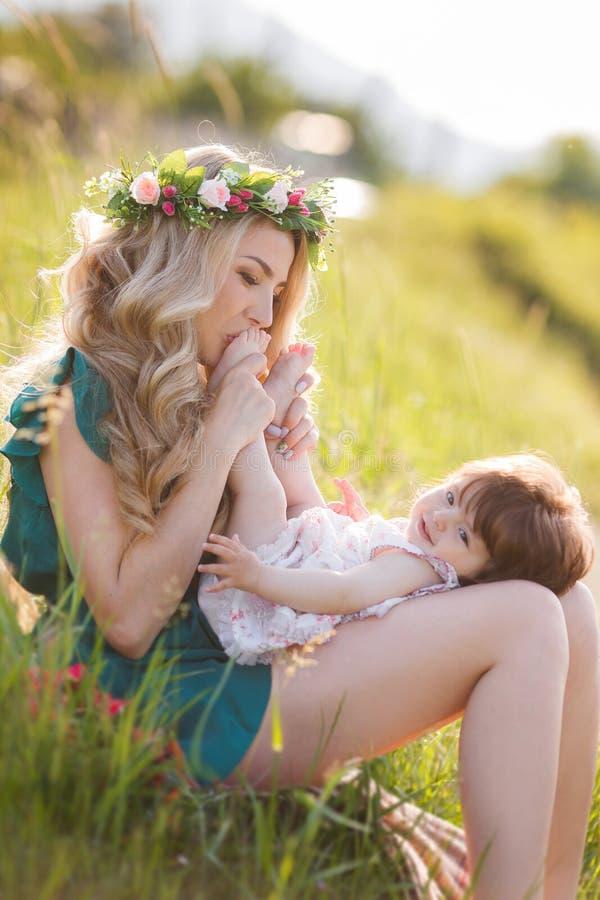 Glückliche Frau mit einem Kind, das auf der Natur stillsteht stockfotografie