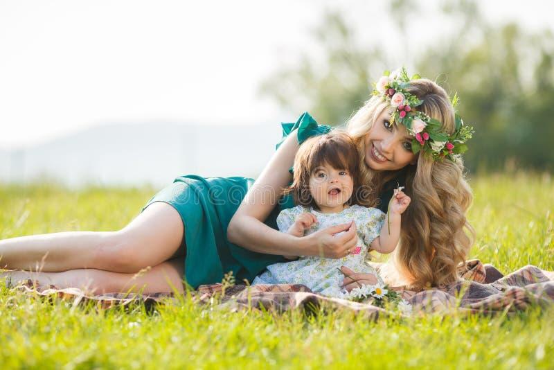 Glückliche Frau mit einem Kind, das auf der Natur stillsteht lizenzfreies stockbild