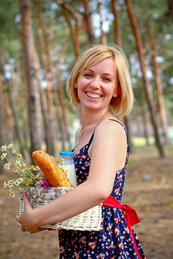 Glückliche Frau mit einem Picknickkorb im Sommer draußen stockfoto
