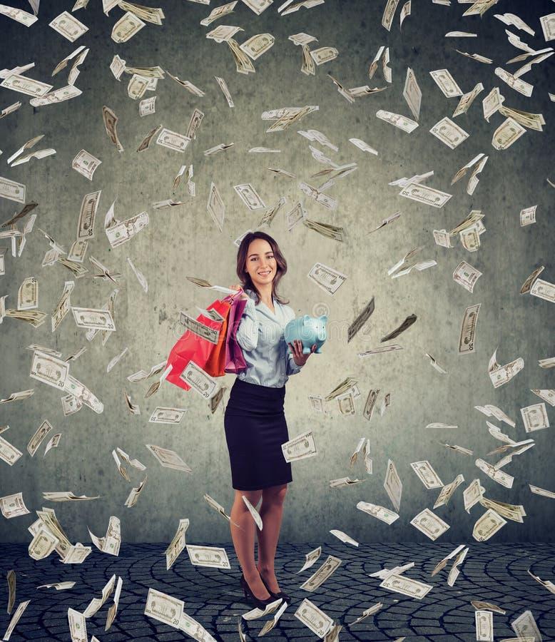 Glückliche Frau mit Einkaufstaschen und das Sparschwein, das unter Geld steht, regnen stockfoto