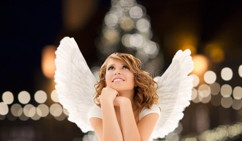 Glückliche Frau mit Engel beflügelt über Weihnachtslichter lizenzfreie stockbilder