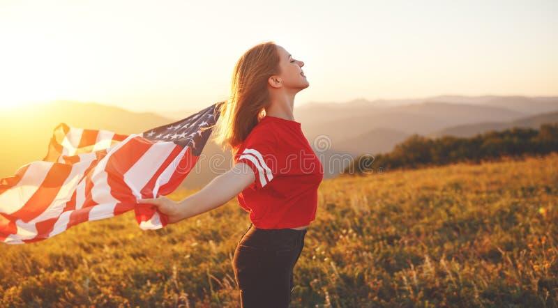 Glückliche Frau mit Flagge von Vereinigten Staaten den Sonnenuntergang auf Na genießend stockbild
