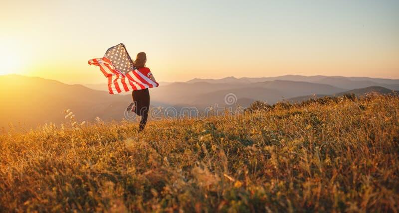 Glückliche Frau mit Flagge von Vereinigten Staaten den Sonnenuntergang auf Na genießend lizenzfreies stockbild