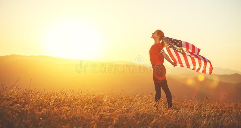 Glückliche Frau mit Flagge von Vereinigten Staaten den Sonnenuntergang auf Na genießend lizenzfreie stockbilder