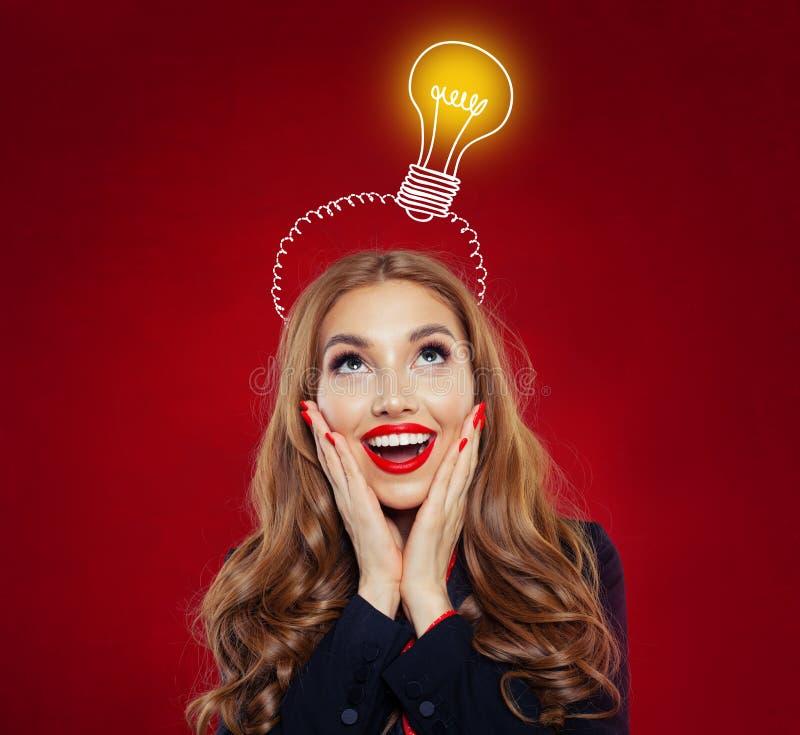 Glückliche Frau mit gelber Glühlampe auf rotem Hintergrund Schönes überraschtes Mädchen Geistesblitz, Ideen, Problem und Lösungsk lizenzfreies stockfoto