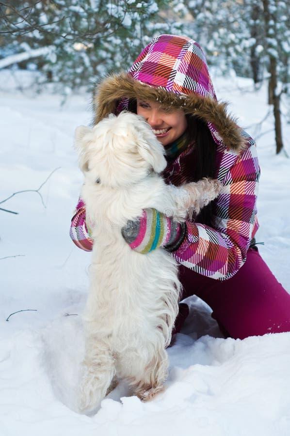 Glückliche Frau mit Hund im Winterwald stockbilder